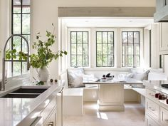 Lovely cottage kitchen features a nook filled with a U shaped built-in banquette doubling as ...