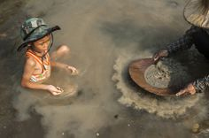 A child plays in the water as his mother pans for gold in Lampang, Thailand. Villagers look for gold in the river every year during the dry season. They are able to make an average around $15 per day. PHOTOGRAPH BY: BORJA SANCHEZ-TRILLO / GETTY IMAGES