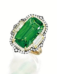 TSAVORITE GARNET AND DIAMOND RING, IVY Centring on a cushion-shaped tsavorite garnet weighing 10.19 carats, flanked on each side by baguette diamonds and framed by circular-cut diamonds, the diamonds together weighing approximately 1.25 carats, mounted in 18 karat yellow and blackened gold, signed.