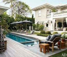 Backyard outdoor lap pool with sun umbrella & wooden banana lounge chairs
