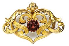 An Art Nouveau Pink tourmaline and carved gold brooch