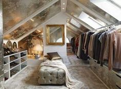 Attic walls are the perfect height for hanging clothes and built-ins; shoe shelves to the left and drawers on the right, with a tufted bench between   Luxurious metallic wallpaper covers the ceiling between painted beams.  The skylights are not the best idea, due to sunlight damage and fading to fabrics, but the natural light would be wonderful.  The exposed chimney brick backdrop is a nice contrast to the gold framed mirror.