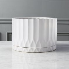 Bright white stoneware elegantly fluted with movement and texture. Built-in tray with drainage hole keeps surfaces protected and provides proper drainage. Perfect for houseplants. drum white planter is a exclusive.
