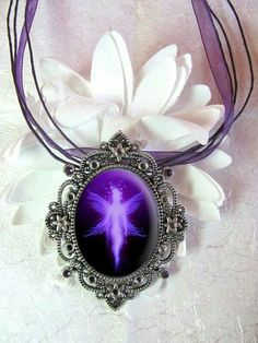 "Victorian inspired angel on purple stone. Stunning design! The angel appears to glow like a star - reminiscent of a ""purple"" star sapphire!"