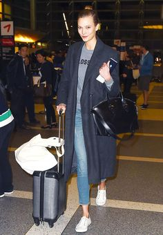 Karlie Kloss wears a graphic sweatshirt, jeans, white sneakers, and a blue trench coat