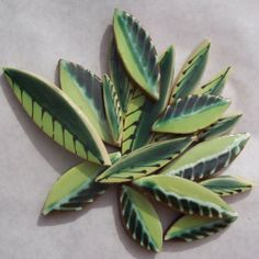 """Handmade mosaic leaf tiles.  Each leaf tile is hand-cut and hand-glazed.  They are flat and unglazed on the bottom.  This set of leaf tiles fit into a 4"""" x 4"""" space."""