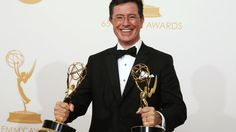 Stephen Colbert poses backstage with his awards for Outstanding Variety Series and Outstanding Writing For A Variety Series at the 65th Primetime Emmy Awards in Los Angeles on Sept. 22, 2013.