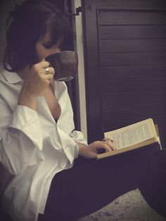 Woman with cup of coffee and book looks perfect :)