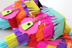 Pinata-Box-Ukelele-Layedred-Die-Cut-Detail-Jpriest Create festive favor boxes that look like pinatas! Jennifer Priest shares how, using the Sizzix eclips2, Tombow adhesive, and Clearsnap ColorBox Ink. The favors will be a HIT at your next fiesta. These are great for papercrafters and card makers, party decor, and any one who likes die cuts. The ukelele on the front is super cute too! #ad