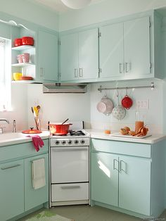 Suble colours in a retro kitchen - little punches of red. This with black/white checkered floor?