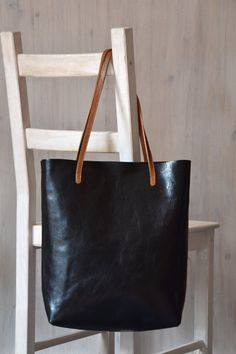 Black leather tote bag MINIMAL CHIC is made of premium, hand finished vegetable tanned leather and handcrafted by me in Poland. This timeless bag is sewn from one piece of leather. Front, rear, and bottom of the bag is one piece of leather, without any additional elements pieced together. The bag can be used every day and it is perfect for any occasion. Great for both work or the university, for a weekend getaway or shopping. A minimalist, functional leather tote, lightweight, durable and…