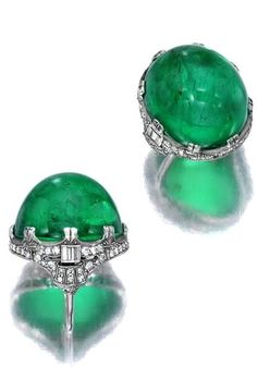 An emerald and diamond ring centering an oval emerald cabochon, measuring approximately x x within a baguette and single-cut diamond surround; emerald weighs approximately: carats; size 4 (with sizer) Emerald Earrings, Emerald Jewelry, High Jewelry, Gems Jewelry, Diamond Jewelry, Jewelry Accessories, Jewelry Design, Dangle Earrings, Bullet Jewelry
