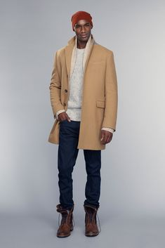 Shop this look on Lookastic:  https://lookastic.com/men/looks/overcoat-shawl-cardigan-crew-neck-sweater-jeans-brogue-boots-beanie/12969  — Orange Beanie  — White Crew-neck Sweater  — Beige Shawl Cardigan  — Camel Overcoat  — Navy Jeans  — Dark Brown Leather Brogue Boots