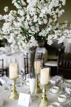 White wedding ideas, white and greenery wedding, white boutonnieres, ranunculus boutonnieres, white centerpieces, white wedding centerpieces, cherry blossom centerpieces. Image Corina V. Photography