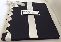 Handmade photo albumto display your special event at anengagement party, bridal shower or weddingin clear archival photo sleeves. The book is covered in cotton fabric with a double faced satin ribbon to match your color scheme (photo shown above depicts a weding theme color of ivory and black). It is a 7-hole binder designed in a corset pattern along the spine.