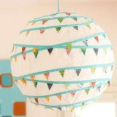 DIY Bunting: These lanterns are so much fun for a colorful wedding. To make this decor option really stand out, don't decorate all of your paper lanterns. Instead, use these garland-themed ones as accents against plain ones.  It'll make them all the more impactful in your event space.