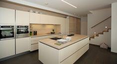 Grifflose Küche in Magnolie matt kombiniert mit Holzdekorelementen in Akazie hell bei Arbeitsplatte, Nischenrückwand, Regal und Schiebetürfronten