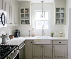Greige cabinets, hanging lantern pendant, glass front cabinets, white subway tile with gray grout