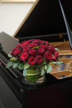 Classic red roses in a low and compact arrangement including a leaf wrap. A perfect companion for this classic piano #FlowerStationNj