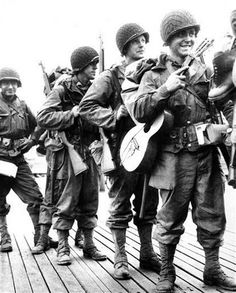 Pvt. Ernest Barker, right, of Eastland, Texas, carries his guitar as he leaves a British port with reinforcements for the Allied beachhead in France in June 1944. (AP Photo) ( England )