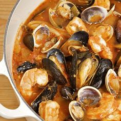 Cioppino Recipe with olive oil, onion, fennel, garlic, fresh thyme, dried oregano, crushed red pepper flakes, bay leaf, saffron, tomatoes with juice, dry white wine, bottled clam juice, cockles, mussels, well scrubbed, fish fillets, large shrimp, Italian parsley leaves, orange zest, orange juice, capers, sourdough bread