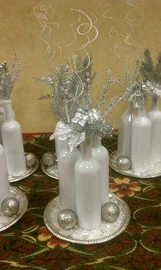 Christmas Party Centerpieces Use dollars tore silver platters, blue beer bottles, and add silver and white accents like painted/glitter pine cones or white yarn balloon balls (mod podge yarn around a balloon let dry then pop it) fill bottles with dollar store decore or painted/glitter branches/twigs