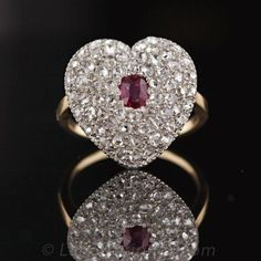 This turn-of-the-century ruby and diamond ring is exquisitely paved with fine high-domed rose cuts of a quality we rarely see. They are very white and with the exception af a couple of small wear chips very high clarity. They fill the heart that is centered with an oval ruby. The top of the ring is fabricated in platinum topped 14 karat yellow gold and has a yellow gold gallery and shank. What a sweetheart of a ring!