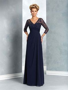 A formal dress with lace overlay yoke and ¾ length sleeves, empire waist, and full-length A-line skirt.