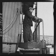 Freight operations on the Indiana Harbor Belt railroad between Chicago, Illinois and Hammond, Indiana. The conductor uses hand brakes on the caboose to stop it as it coasts down a siding, 1940s.  Photo by Jack Delano. LOC