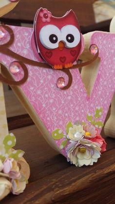 Nome  Lívia em MDF decorado com a  técnica de scrapdecor, letras  foradas com  papéis de scrapboook, flores feitas  a partir de  furadores. Menina  com  flores comprada  no site da silhuette Design. Coruja Rosa no galho.
