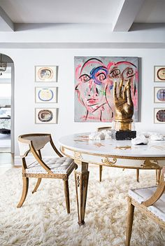 White and gold dining room with white shag rug and abstract art