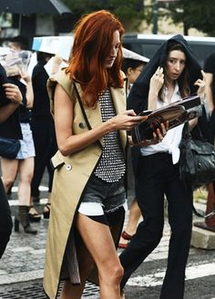 Besides that fact that the color combo makes her gorgeous red hair pop, the outfit makes a stir even though it is neutral colored. Cut off jeans with the pockets showing, and sleeveless long jacket are a contradiction of terms that actually make sense.