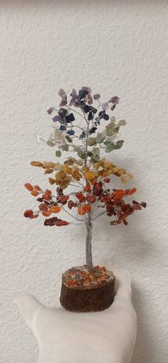 Este producto representa un árbol, con su base de madera compuesta por chip de diferentes minerales, el tronco de este árbol está hecho con alambre de color plata brillante, y sus hojas están representadas con chip de un tamaño aproximado de 5mm.  El rodado que hemos seleccionado para realizar este árbol son varios, Jaspe rojo, carneola, calcita amarilla, cuarzo verde, sodalita, cuarzo, amatista, representando los 7 chakras.  Características del arbol de madera  Mineral: 7 chacras… Color Plata, Base, Home Decor, Wooden Tree, Yellow Girl Nurseries, Glow, Wire, Minerals, Leaves