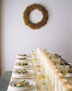 Candlelit Table. A row of cream-colored pillar candles down the middle of the table. Branch wreath hung above.