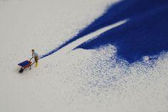 Liliana Porter, Forced Labor (blue sand) II (2008)  Figurine and blue sand on shelf  10 ¼ x 43 ½ x 3 ½  Part of the Forced Labor series