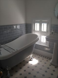 Grey and white bathroom. Painted roll top bath and original styles victorian floor tiles.