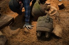 Archaeologist Anna Cohen works in the central area of the cache, where ritual vessels were found arrayed around a stone vulture.  PHOTOGRAPH BY DAVE YODER, NATIONAL GEOGRAPHIC