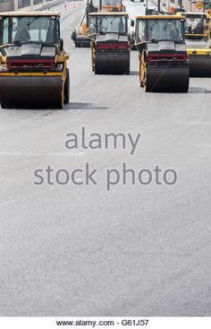 Steam rollers machines compacting fresh asphalt during road construction works - Stock Image