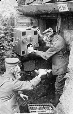 German soldiers wearing respirators as they place carrier pigeons into a gas-proof chamber, presumably during an anti-gas drill.