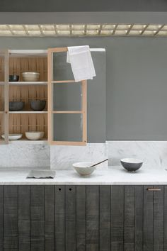 Smooth honed Carrara marble worktops, textured Sebastian Cox cabinets and handmade ceramic bowls by deVOL