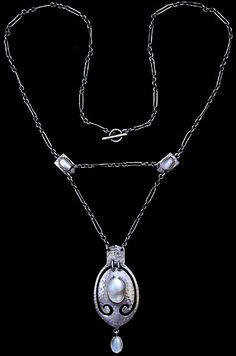 MURRLE BENNETT & Co. (1896-1914)  An Arts & Crafts hammered silver necklace set with a central mother of pearl plaque in a golden setting and with a pearl drop and two silver spacers, also   set with mother-of-pearl plaques in golden settings, to the original chain and clasp.  Anglo/German c.1900. Marks for MB & Co. and 950. (Necklace case)  Size: Length of pendant 5 cm. Width 2.2 cm. Approx. necklace length 42.5 cm.