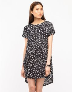 """Relaxed tee dress with a restrained gothic sensibility from Evil Twin. Features all over fluctuating """"X"""" pattern on breathable viscose fabric, contrast back zip, and a gently rounded asymmetric hem.  •Relaxed tee dress with all over X print •Breath"""