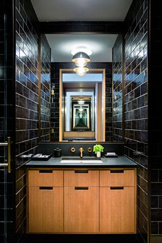 Walls in a guest bathroom are finished in black glazed brick tile from Urban Archeology. The Dome sconce is by Allied Maker. (Photo: Brittany Ambridge)