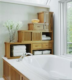 Make use of the space between the bathtub and ceiling by adding storage options. Here, stock cabinets and cubbies stack up to create an interesting stairstep configuration that allows the space to be used for both storage and display. Use the open cubbies for storing towels for easy access.