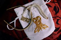 Wedding accessories by Nomen: Bridal necklace is made of pearls, and golden ornaments holding tiny pearls. Hairband made of gold twisted string for holding veil at place. Gold corset-shaped decoration on bride's silk handbag is handmade, and designed by us.