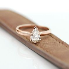 This beautifully hand crafted solitaire engagement ring is set with a pear shaped diamond and surrounded by 14K Rose Gold. Shop this ring online at MiaDonna.com