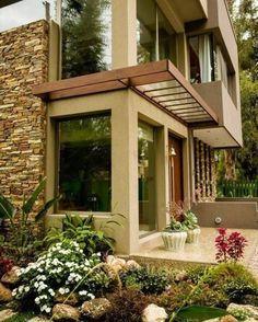 Nesse projeto, os donos da casa optaram por uma fachada com cores semelhantes à da natureza, para valorizar ainda mais o paisagismo e deixar o jardim ainda mais aconchegante.