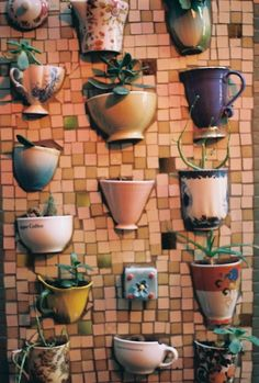 DIY Inspo: Mosaic wall with embedded teacups for a succulent garden.
