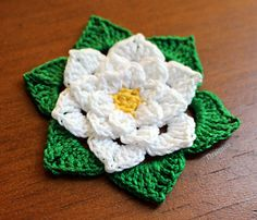 "This flower is 9 rounds and measures about 2 1/2"". Materials needed are a small amount of size 10 thread in 3 colors and a 1.75 mm hook."