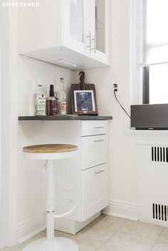 Brooklyn kitchen features deep IKEA drawer storage and a translucent upper cabinet displaying glass and barware. The new section of countertop doubles as a mini eat-in kitchen nook with it's extra overhang.